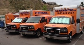 Water Damage Restoration Vans And Trucks At Job Site