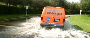 Water Damage Van Driving Down Flooded Street